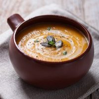 Homemade tasty creamy pumpkin soup puree in a bowl on a wooden background